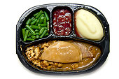 A microwave/TV dinner. Includes turkey & stuffing, mashed potatoes, cherry cobbler, and green beans. Isolated on white.