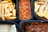 Selection of frozen, processed, ready made foods, consisting of potato chips, mince, lasagna in black, plastic containers . Microwave meals ready to heat up .
