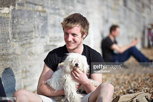 Mid 20's male sat on the beach with a puppy