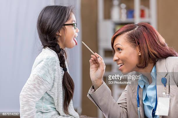 Mid adult African American pediatrician examines young patient