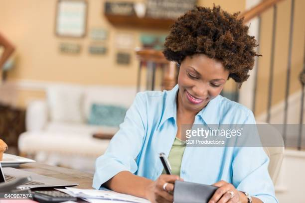 Mid adult African American woman balances checkbook in home office
