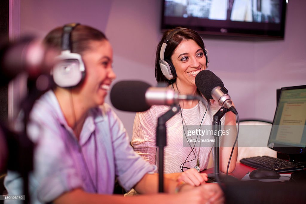 Mid adult and young women broadcasting in recording studio