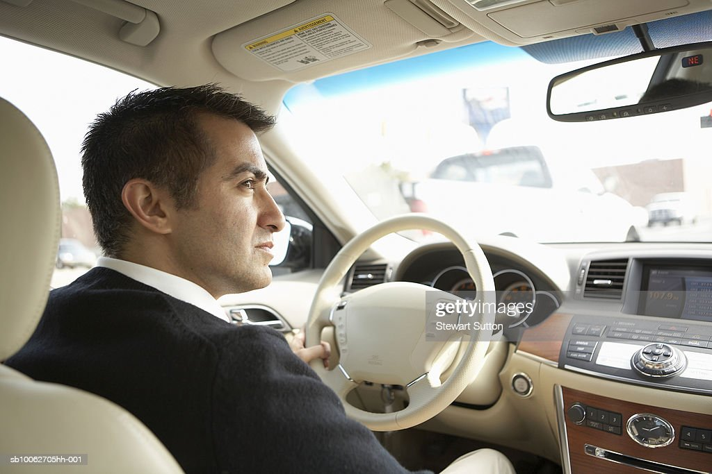 Mid adult business man driving car, profile : Stock Photo
