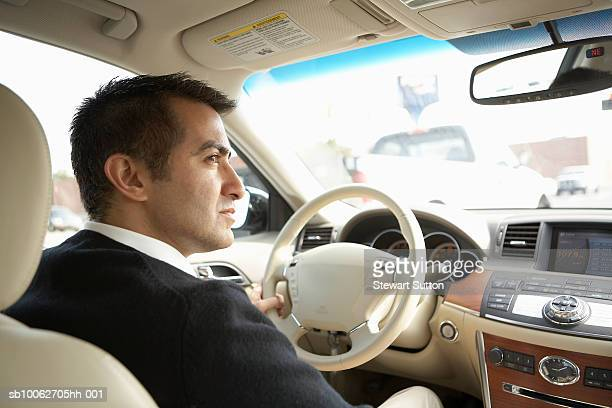 Mid adult business man driving car, profile