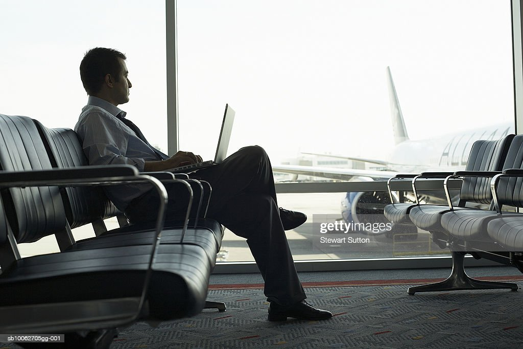 Mid adult business man sitting at airport, using laptop, airplane behind window : Stock Photo