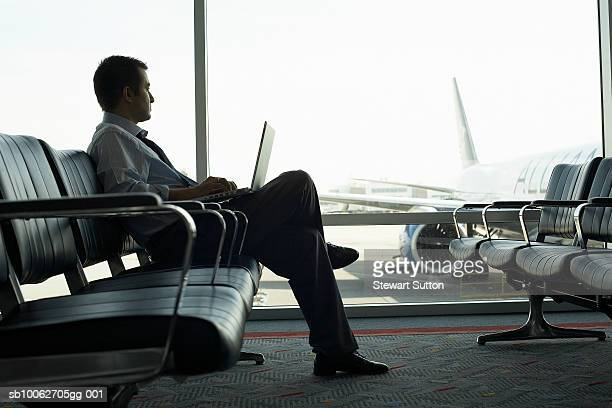 Mid adult business man sitting at airport, using laptop, airplane behind window