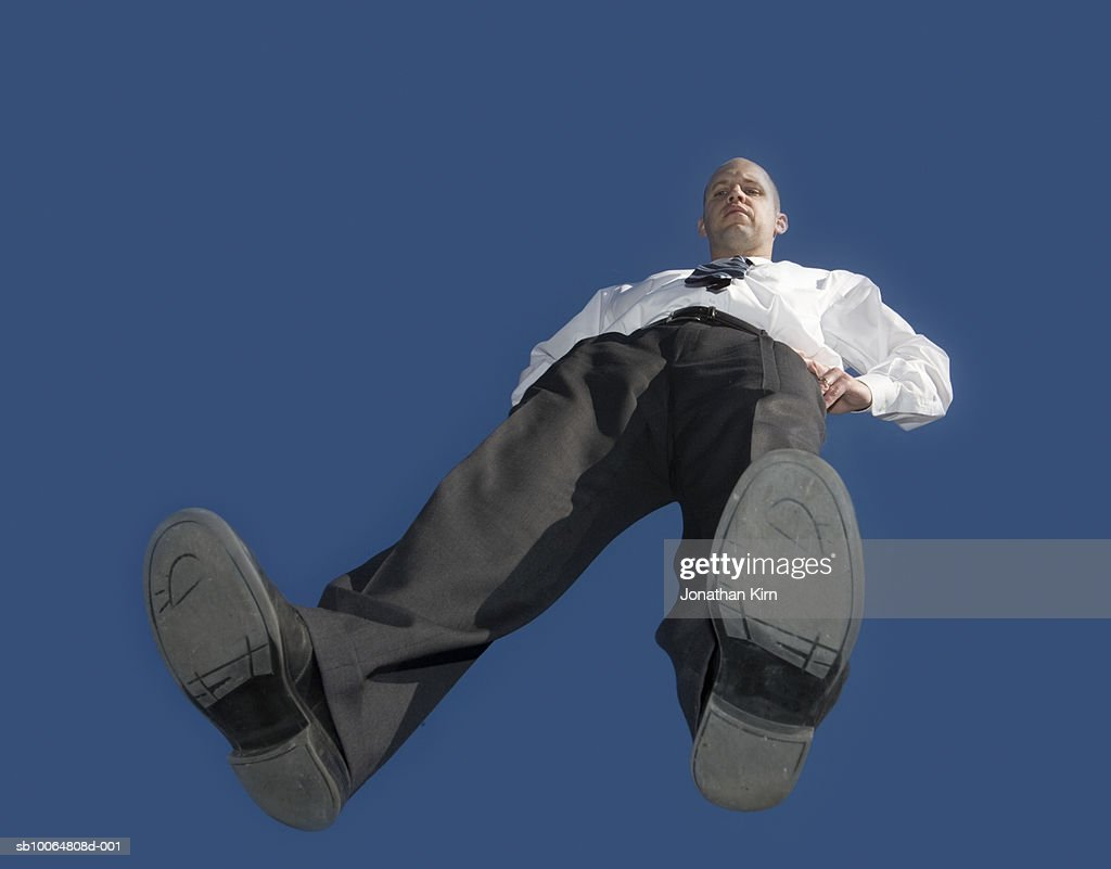 Mid adult business man standing on glass, blue sky, view from below