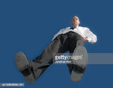 Mid adult business man standing on glass, blue sky, view from below : Stock Photo