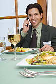 Mid adult business man talking on mobile at restaurant table