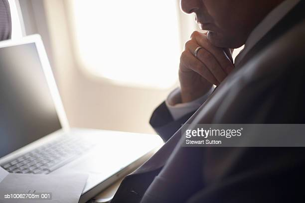 Mid adult business man working on laptop sitting in airplane