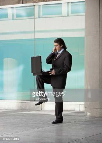 Mid Adult Businessman Balancing Briefcase on One Leg and Using Mobile Phone