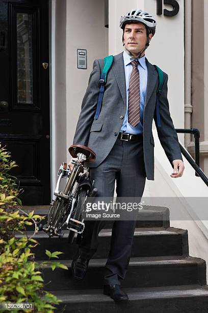 Mid adult businessman carrying folding bicycle down steps