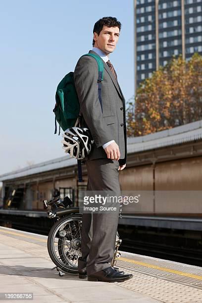 Mitte Erwachsene Geschäftsmann tragen Falten Fahrrad auf dem Bahnsteig