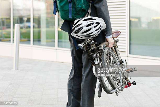 Mid adult businessman carrying folding bicycle