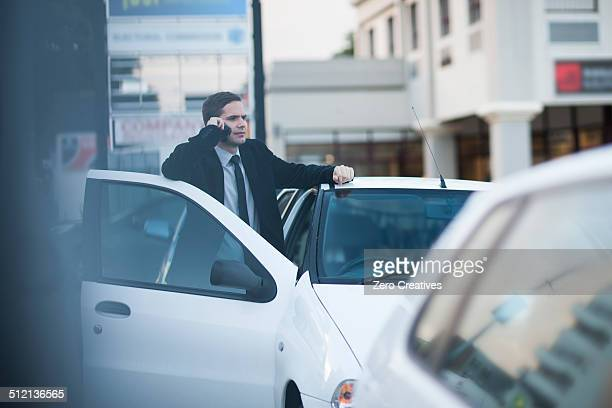 Mid adult businessman chatting on smartphone in city traffic jam