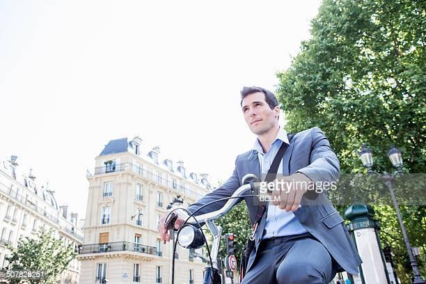Mid adult businessman commuting on bicycle, Paris, France