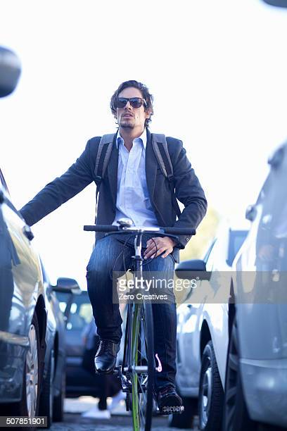 Mid adult businessman cycling in traffic congestion