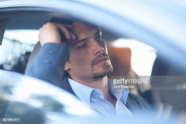 Mid adult businessman driving in traffic congestion
