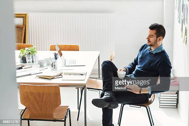 Mid adult businessman having coffee at desk in office