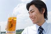 Mid adult businessman holding mug of beer