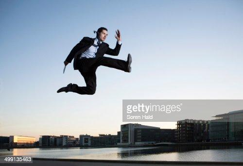 Mid adult businessman jumping mid air, Copenhagen harbor, Denmark