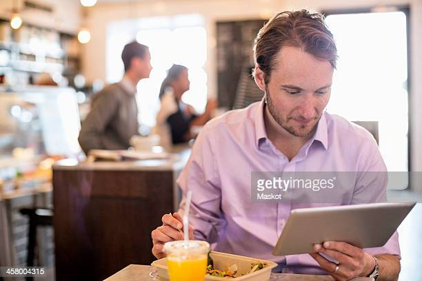 Mid adult businessman looking at digital tablet while having breakfast at table in restaurant