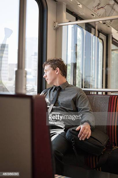 Mid adult businessman looking out of train carriage window