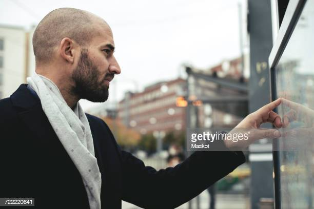 Mid adult businessman reading map in city