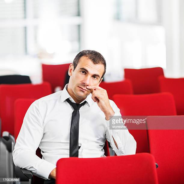 Mid adult businessman sitting alone on a seminar.