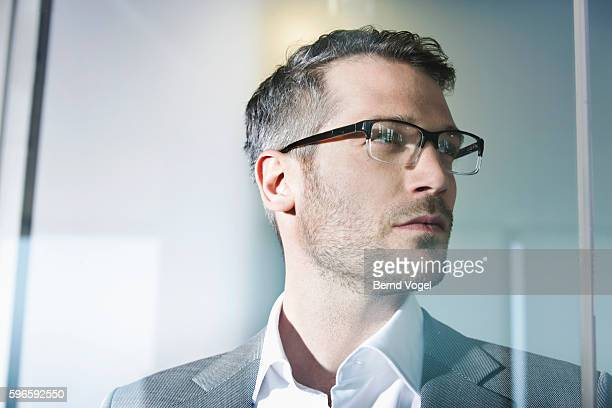 Mid adult businessman standing behind glass screen