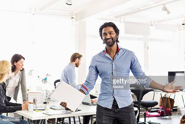 Mid adult businessman standing with arms outstretched in office