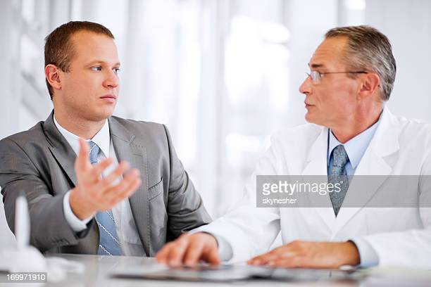 Mid adult businessman talking to a mature doctor.