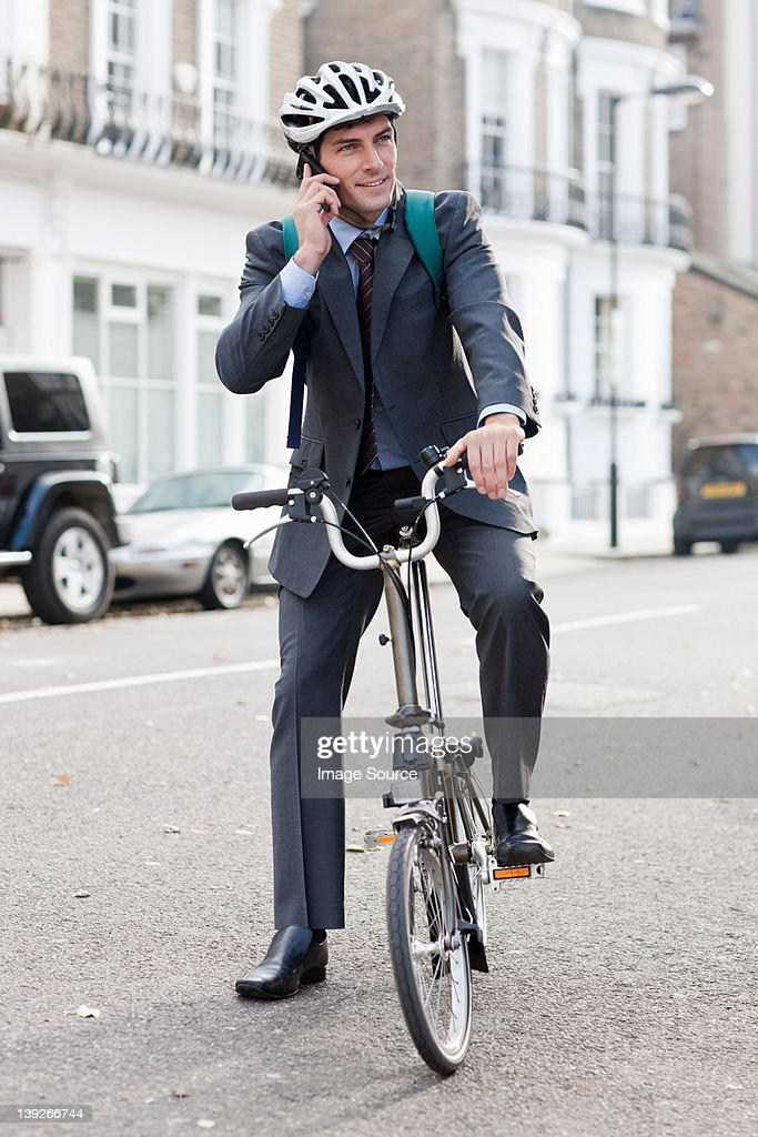 Mid adult businessman using cellphone on bicycle