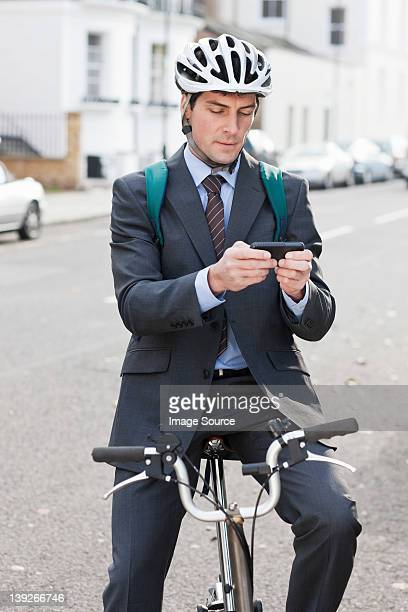 Mid adult businessman using cellphone to text on bicycle