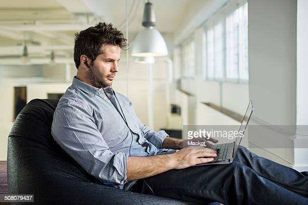 Mid adult businessman using laptop while sitting on bean bag in office