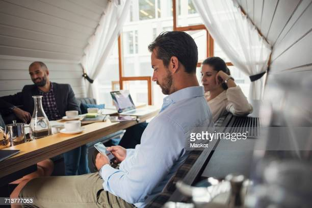 Mid adult businessman using mobile phone at table during office meeting
