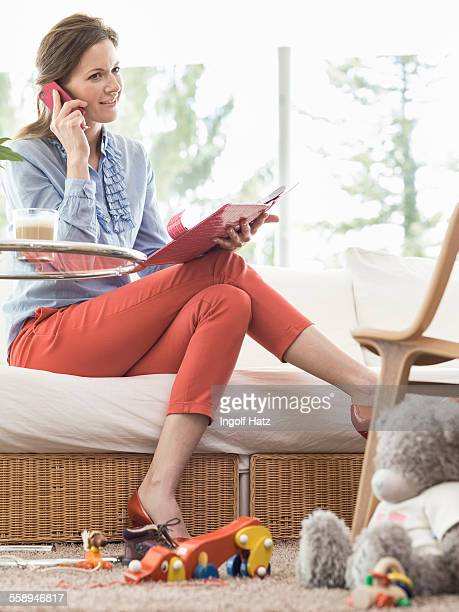 Mid adult businesswoman at home talking on smartphone with toys scattered on floor