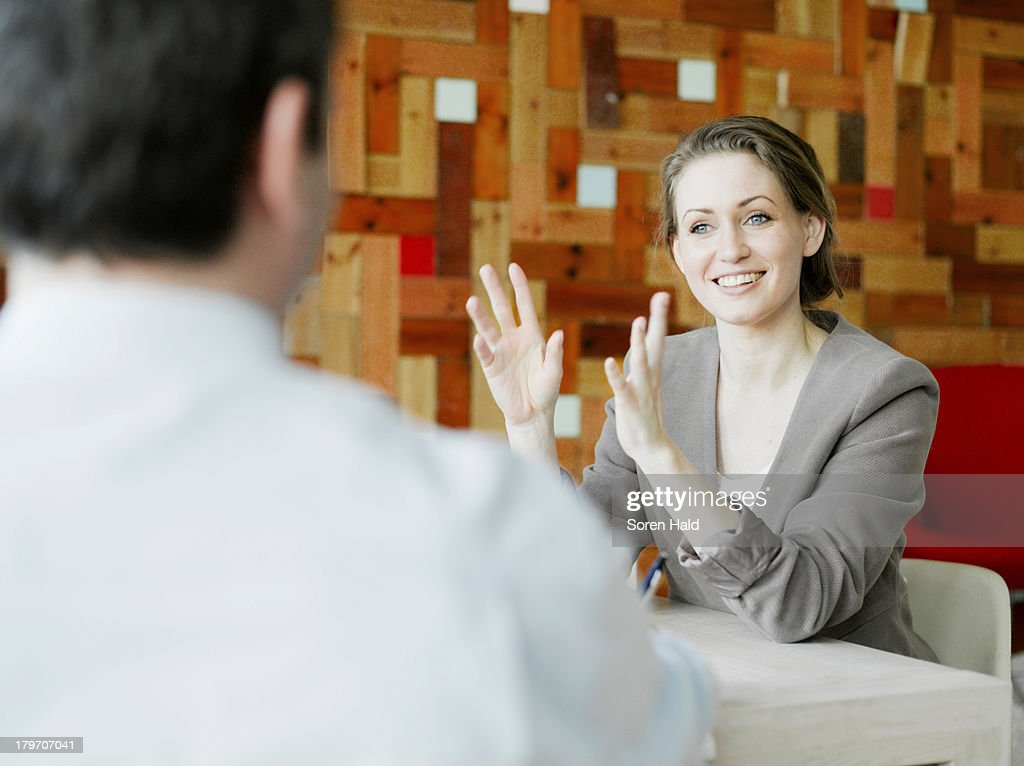 Mid adult businesswoman explaining in meeting