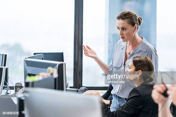 Mid adult businesswoman gesturing with female employy at computer