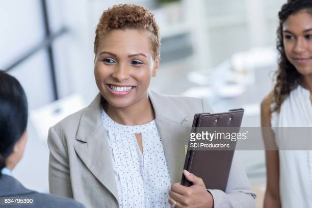 Mid adult businesswoman greets client