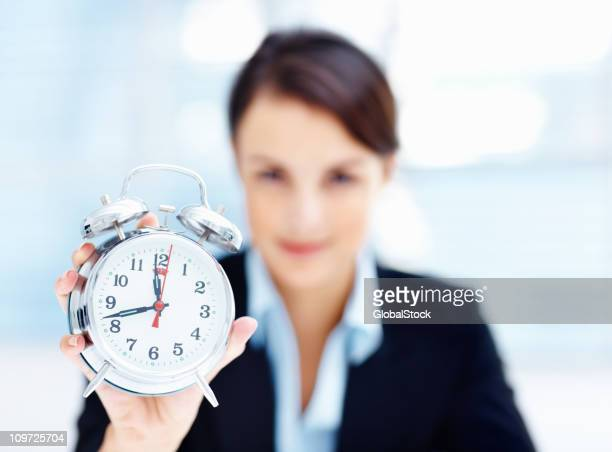 Mid adult businesswoman holding an alarm clock