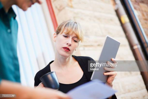 Mid adult businesswoman holding digital tablet and coffee cup while discussing with colleague outside office
