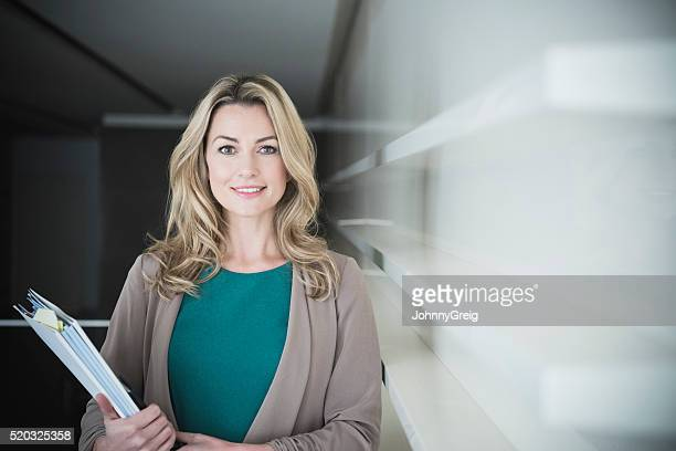Mid adult businesswoman holding file at work