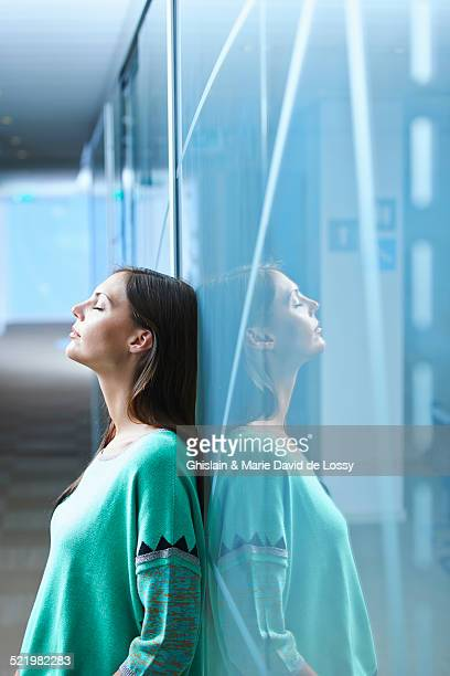 Mid adult businesswoman leaning against glass wall in office with eyes closed