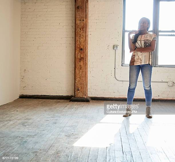 Mid adult businesswoman looking up in empty new office