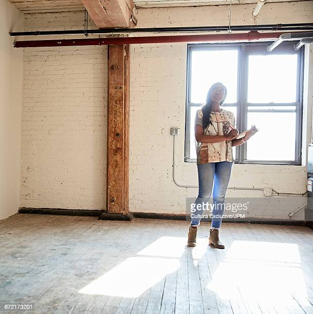 Mid adult businesswoman making clipboard notes in empty new office