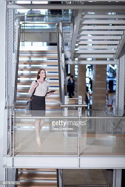 Mid adult businesswoman on stairway in conference centre