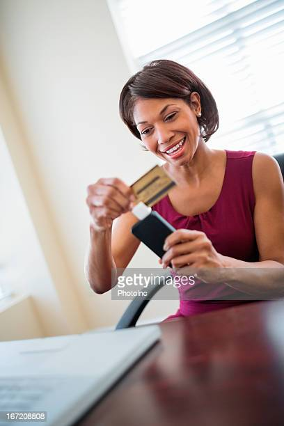 Mid Adult Businesswoman Swiping Credit Card