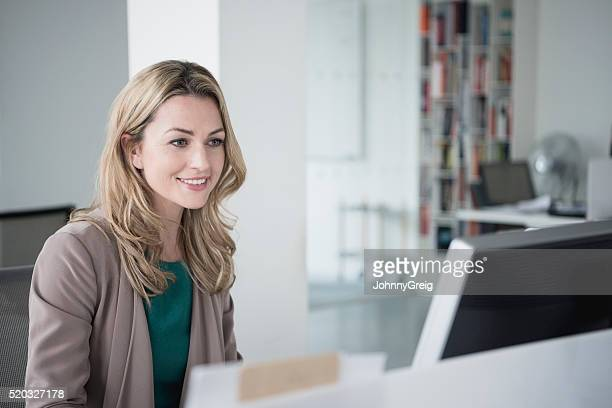 Mid adult businesswoman using desktop computer, smiling
