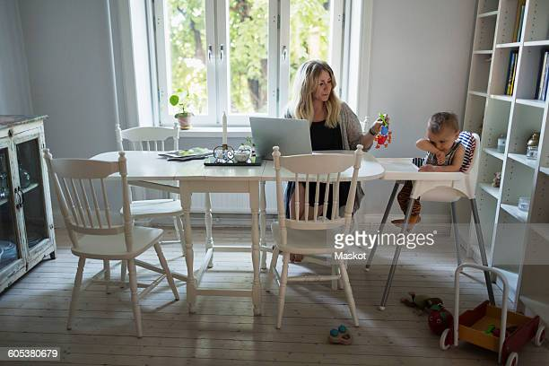 Mid adult businesswoman using laptop while taking care of baby at home